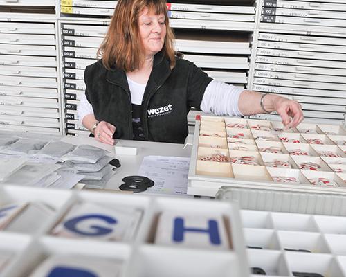 Mitarbeiterin sortiert Einzelbuchstaben aus Folie