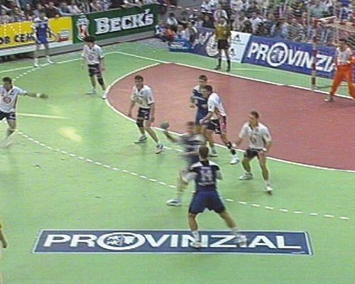 Werbung an Bande und auf Boden eines Handballspiels